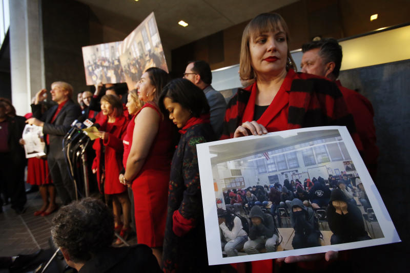 United Teachers Los Angeles union representative Julie Van Winkle, right, holds a photograph with a class of 39 students covering their faces to avoid the need of parental releases, during a news conference outside the Los Angeles Unified School District headquarters in Los Angeles Friday, Jan. 11, 2019. A massive teachers strike in Los Angeles is still planned for Monday after a union rejected a new offer from the nation's second-largest school district and declared an impasse following 21 months of increasingly heated negotiations. (AP Photo/Damian Dovarganes)