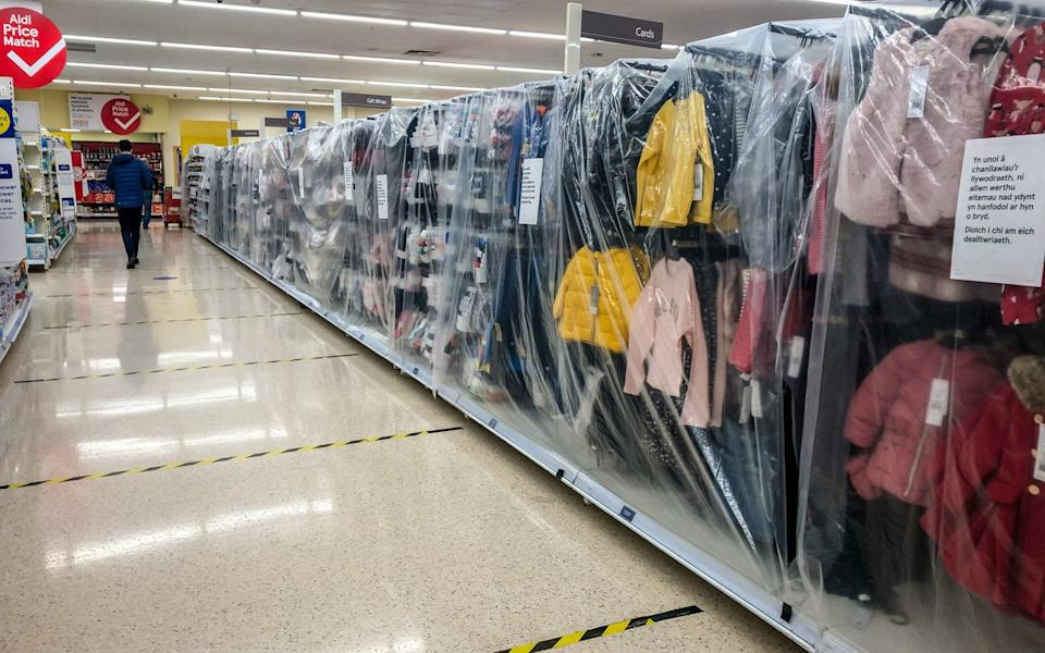 "Childrens clothes in a supermarket near Cardiff are deemed non-essential items and are cordoned off as Wales entered a two-week ""firebreak""  - PA"