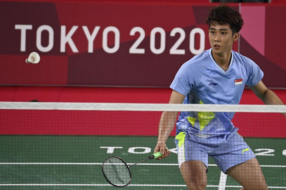Singapore shuttler Loh Kean Yew hits a shot to Indonesia's Jonatan Christie in their men's singles group stage match at the 2020 Tokyo Olympics.