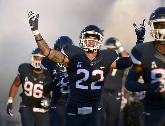 FILE - In this Aug. 30, 2018, file photo, Connecticut linebacker Eli Thomas (22) raises his arms to the crowd as his team enters the field for their season-opening NCAA college football game against Central Florida in East Hartford, Conn. Thomas, who overcame a stroke to return to school, is among the first six athletes named as finalists for the Hartford HealthCare Courage Award. (AP Photo/Stephen Dunn, File)