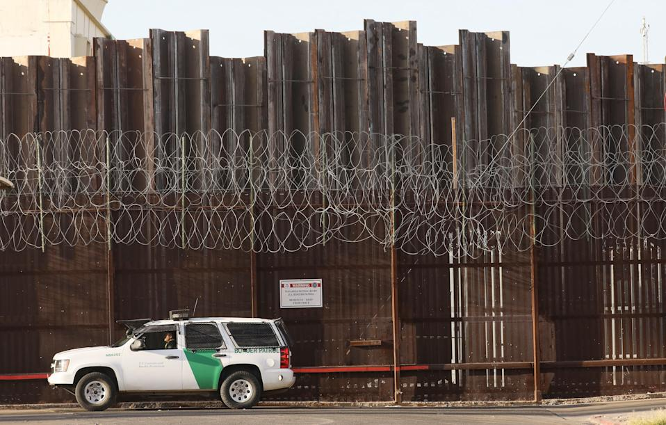 A Border Patrol agent in front of the U.S.-Mexico border barrier