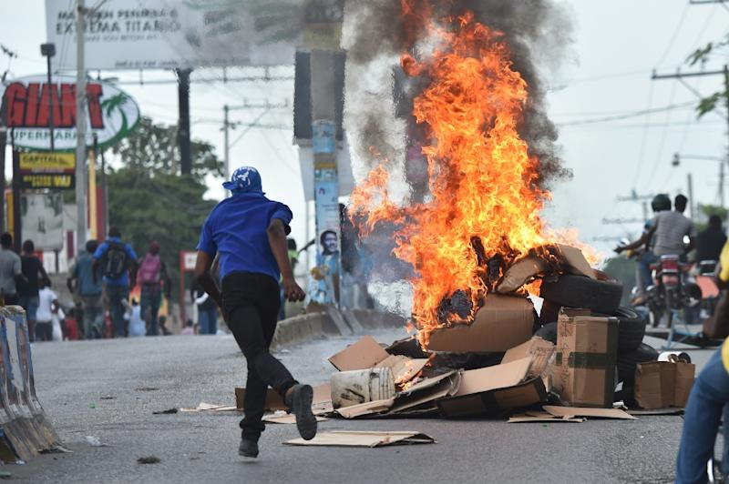 Demonstrators protesting the election of Jovenel Moise as new president of Haiti flee during clashes with police, in Port-au-Prince, on November 30, 2016 (AFP Photo/Hector Retamal)