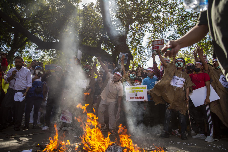 Chin refugees from Myanmar shout slogans as the mock coffins of Commander in chief, Senior Gen. Min Aung Hlaing and Chinese President Xi Jinping are set on fire during a protest against military coup in Myanmar, in New Delhi, India, Wednesday, March 3, 2021. (AP Photo/Altaf Qadri)