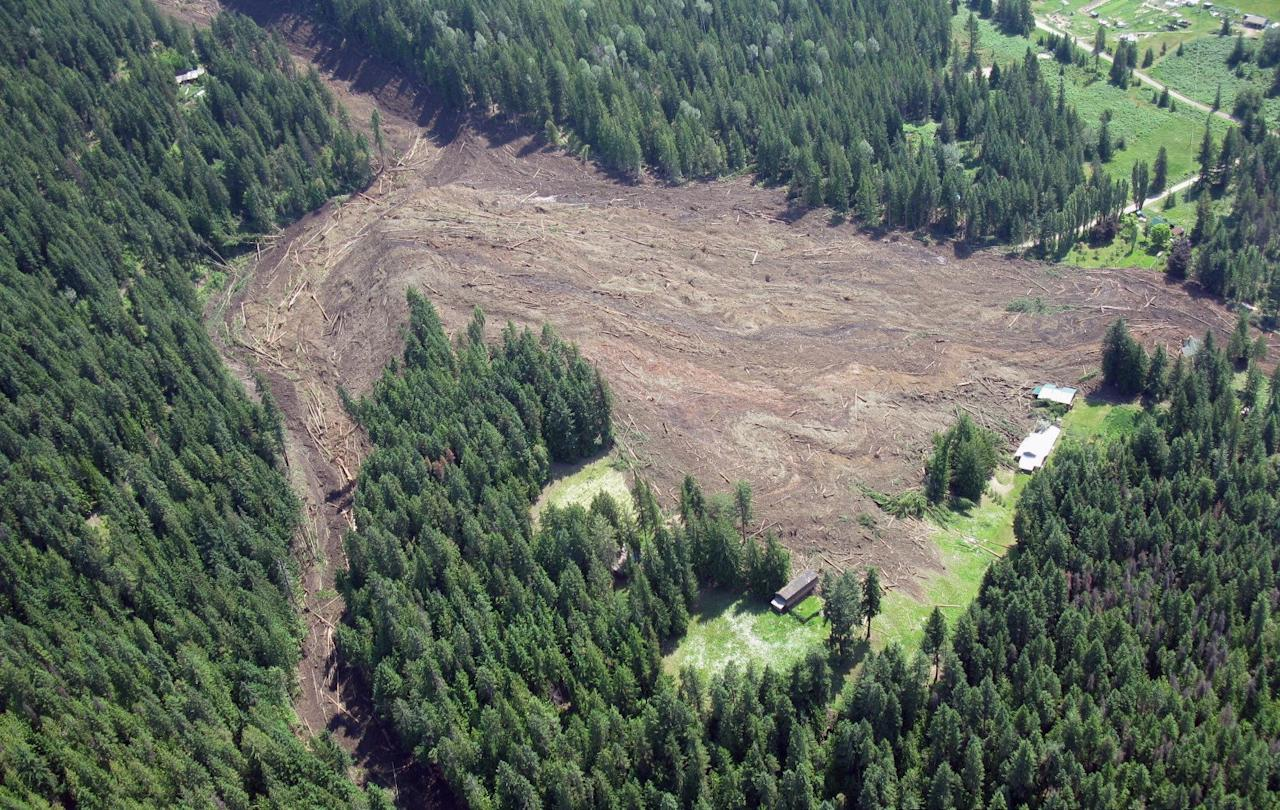 The Johnsons landing landslide is shown in this Thursday July 12, 2012 photo provided by Emergency BC. Four people are still unaccounted for nearly 24 hours after a wall of rock, mud and trees cascaded down the side of a mountain above the shores of Kootenay Lake, tearing through the tiny community of Johnsons Landing, about 70 kilometres northeast of Nelson. At least three homes in the southeastern B.C. hamlet are engulfed by the muck, which is unstable and shifting, prompting searchers to call off rescue efforts at least once on Thursday afternoon. Emergency crews met at dawn Friday to consider the most efficient and effective way to search the massive mudslide for possible victims. (AP Photo/Emergency BC via The Canadian Press) HANDOUT PHOTO; ONE TIME USE ONLY; NO ARCHIVES; NO Sales