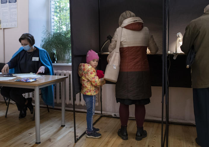 A child looks out of booth at a polling station during parliamentary elections in Vilnius, Lithuania, Sunday, Oct. 11, 2020. Polls opened Sunday for the first round of national election in Lithuania, where voters will renew the 141-seat parliament and the ruling four-party coalition is widely expected to face a stiff challenge from the opposition to remain in office. (AP Photo/Mindaugas Kulbis)