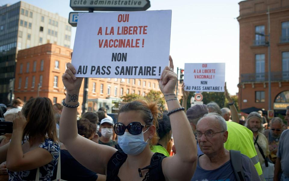 A woman holds a placard reading 'Yes to vaccination freedom, no to the health pass' - Getty