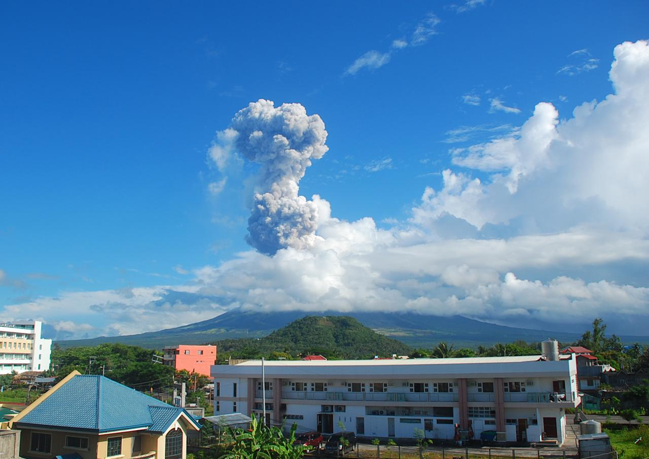 A cloud of volcanic ash shoots up to the sky as Mayon volcano, one of the Philippines' most active volcanoes, erupts after daybreak, viewed from Legazpi city in Albay province in the central Philippines, Tuesday, May 7, 2013. At least five climbers were killed and more than a dozen others are trapped near the crater in its first eruption in three years, officials said. Rescue teams and helicopters were sent to Mayon volcano to bring out the dead. (AP Photo/Allan Imperial)