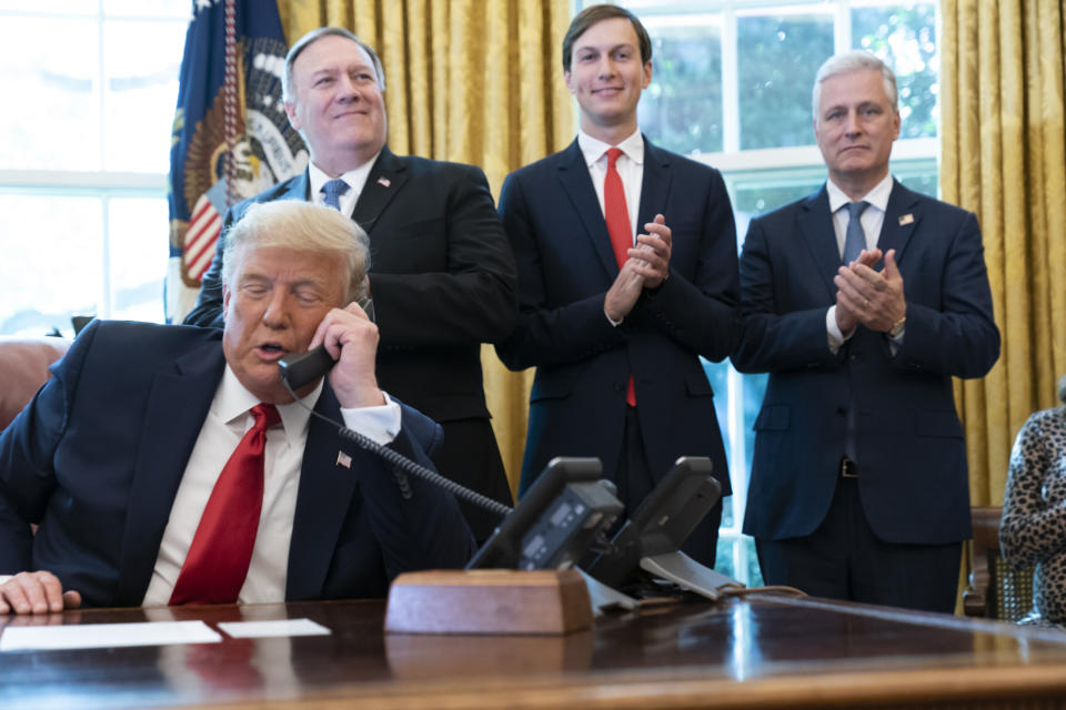 President Donald Trump talks on a phone call with the leaders of Sudan and Israel, as Secretary of State Mike Pompeo, left, White House senior adviser Jared Kushner, and National Security Adviser Robert O'Brien, applaud in the Oval Office of the White House, Friday, Oct. 23, 2020, in Washington. (AP Photo/Alex Brandon)