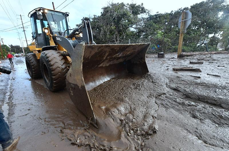 A bulldozer clears mud off the road near a flooded section of US 101 freeway near the San Ysidro exit in Montecito, California on January 9, 2018 (AFP Photo/FREDERIC J. BROWN)