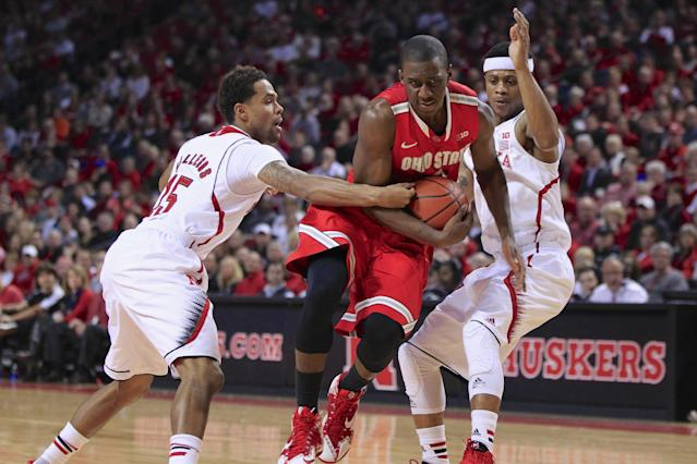 Ohio State guard Shannon Scott, center, drives to the basket between Nebraska's Ray Gallegos, left, and Nebraska's Deverell Biggs, right, in the first half of an NCAA college basketball game in Lincoln, Neb., Monday, Jan. 20, 2014. (AP Photo/Nati Harnik)