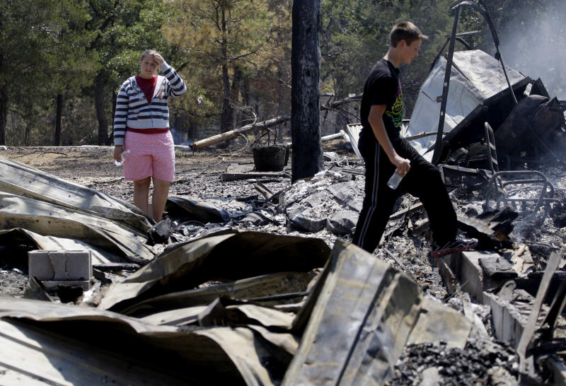 Laura Clements, left, and brother Ben, survey their fire-destroyed home, Tuesday, Sept. 6, 2011, in Bastrop, Texas. The Clements lost their home to fires Monday. More than 1,000 homes have been destroyed in at least 57 wildfires across rain-starved Texas, most of them in one devastating blaze near Austin that is still raging out of control, officials said Tuesday.  (AP Photo/Eric Gay)