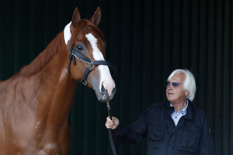 Trainer Bob Baffert walks Kentucky Derby winner Justify through a barn before the Preakness Stakes. (USAT)