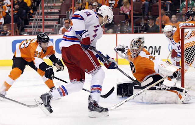 Philadelphia Flyers' Steve Mason, front right, looks to stop the shot by New York Rangers' Rick Nash, center, with Flyers' Mark Streit, left, of Switzerland, reaching for the puck with his stick during the second period in Game 4 of an NHL hockey first-round playoff series on Friday, April 25, 2014, in Philadelphia. (AP Photo/Chris Szagola)