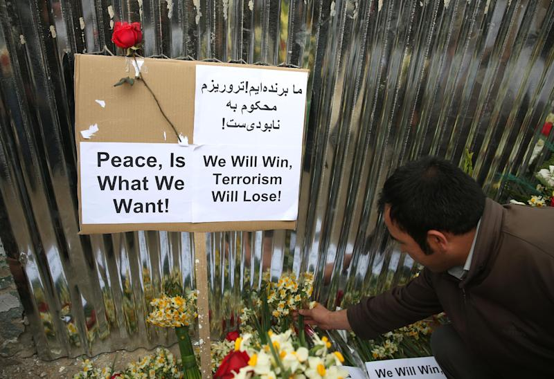An Afghan member of a civil society organization puts flowers outside of the La Taverna du Liban restaurant, during an anti terrorism demonstration in Kabul, Afghanistan, Sunday, Jan. 19, 2014. Hundreds of Afghans gathered outside a Lebanese restaurant in Kabul on Sunday to protest against Taliban attack that killed 21 people. The assault Friday by a Taliban bomber and two gunmen against the La Taverna du Liban restaurant was deadliest single attack against foreign civilians in the course of a nearly 13-year U.S.-led war there now approaching its end. They chanted slogans against terrorism as they laid flowers at the site of the attack. The dead included 13 foreigners and eight Afghans, all civilians. The attack came as security has been deteriorating and apprehension has been growing among Afghans over their country's future as U.S.-led foreign forces prepare for a final withdrawal at the end of the year. (AP Photo/Massoud Hossaini)