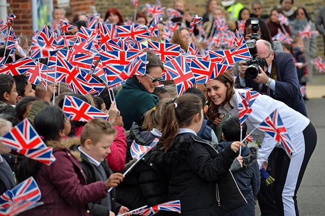 Kate Middleton hudled up with fans on the sidelines with mini Union Jack flags all around