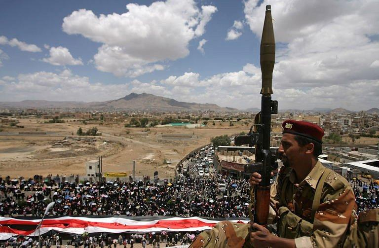 A Yemeni army soldier stands guard in Sanaa during a parade by anti-government protesters. A Gulf mediator flew out on Sunday after failing to secure Yemeni President Ali Abdullah Saleh's signature on a transition deal for him to quit office, although his ruling party signed the accord