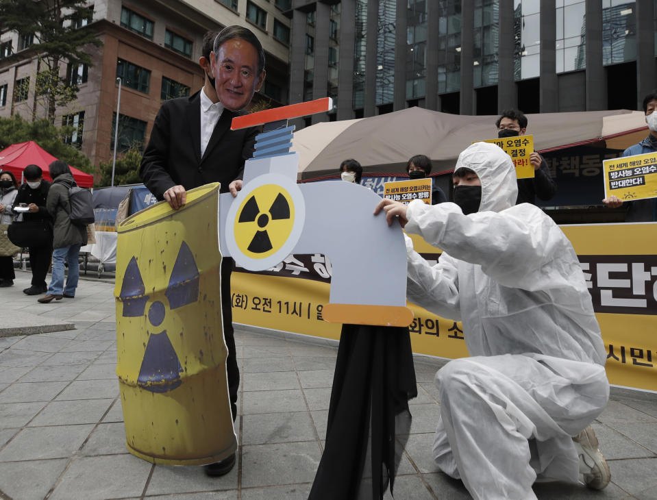 An environmental activist wearing a mask of Japanese Prime Minister Yoshihide Suga performs to denounce the Japanese government's decision on Fukushima water, near the Japanese embassy in Seoul, South Korea, Tuesday, April 13, 2021. Japan's government decided Tuesday to start releasing massive amounts of treated radioactive water from the wrecked Fukushima nuclear plant into the Pacific Ocean in two years - an option fiercely opposed by local fishermen and residents. (AP Photo/Lee Jin-man)