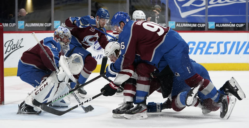 Arizona Coyotes center Christian Dvorak, bottom right, is knocked over while driving to the net by Colorado Avalanche right wing Mikko Rantanen, top right, as Avalanche goaltender Philipp Grubauer follows the puck in the second period of an NHL hockey game Monday, March 8, 2021, in downtown Denver. (AP Photo/David Zalubowski)