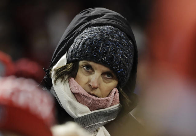 FILE - In this Oct. 23, 2018, file photo, a bundled-up spectator watches Game 1 of baseball's World Series between the Boston Red Sox and the Los Angeles Dodgers in Boston. The 2020 regular season was scheduled to end on Sept. 27, but it's possible games could be pushed well into October or November. That probably wouldn't be a huge problem in warm-weather cities like Houston and Los Angeles or places with retractable roofs, such as Toronto. But November night games in Minneapolis, Chicago or Boston? Brrrrr. (AP Photo/David J. Phillip, File)