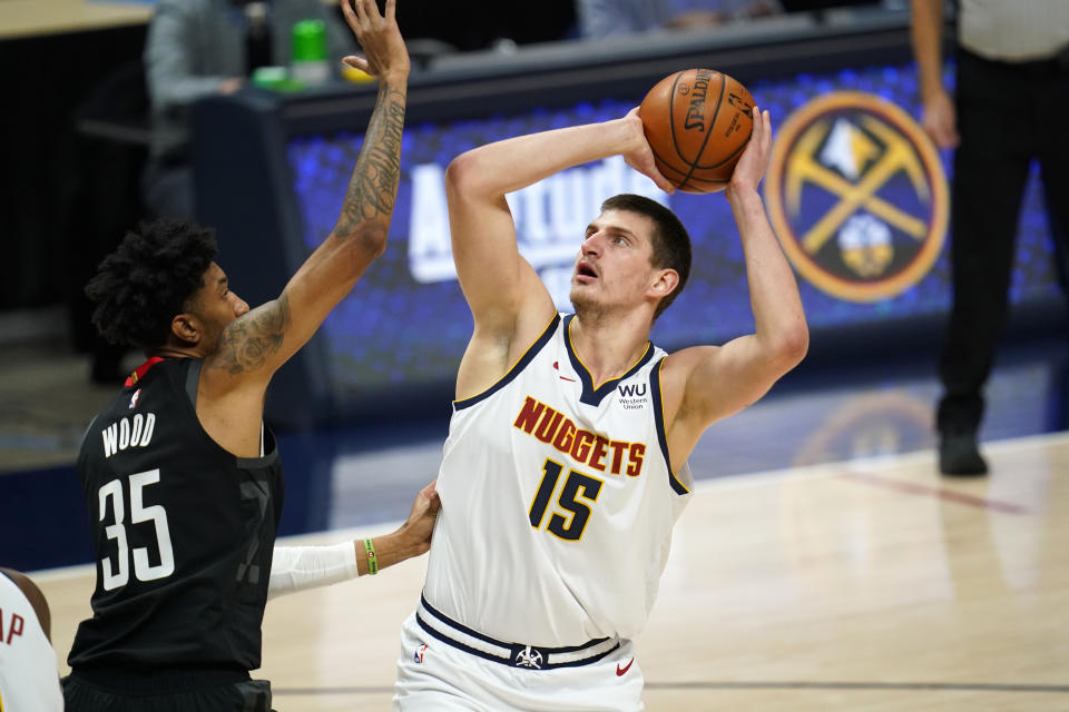 Denver Nuggets center Nikola Jokic, right, shoots over Houston Rockets forward Christian Wood