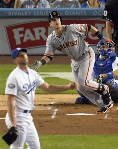 San Francisco Giants' Buster Posey, center, watches his solo home run off Los Angeles Dodgers starting pitcher Chris Capuano, left, during the second inning of a baseball game, Tuesday, Oct. 2, 2012, in Los Angeles. Dodgers catcher A.J. Ellis is at right. (AP Photo/Mark J. Terrill)
