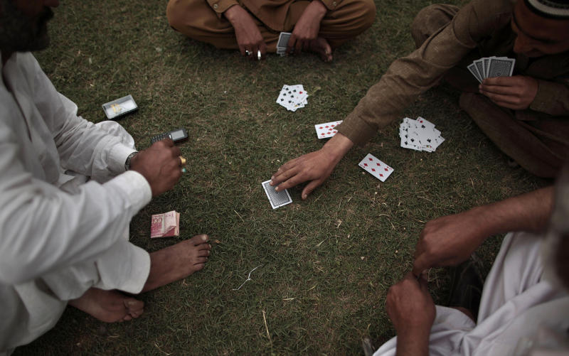 "In this Wednesday, March 20, 2013, photo, Pakistani men play cards in a field in a neighborhood on the outskirts of Islamabad, Pakistan. For months, the Supreme Court's Chief Justice Iftikhar Chaudhry has been leading special hearings on Karachi's crime, berating the city's top police officers for failing to act. The past week, he demanded they move in to clean up so-called ""no-go"" areas _ entire neighborhoods where police fear to tread _ according to local press reports. (AP Photo/Nathalie Bardou)"