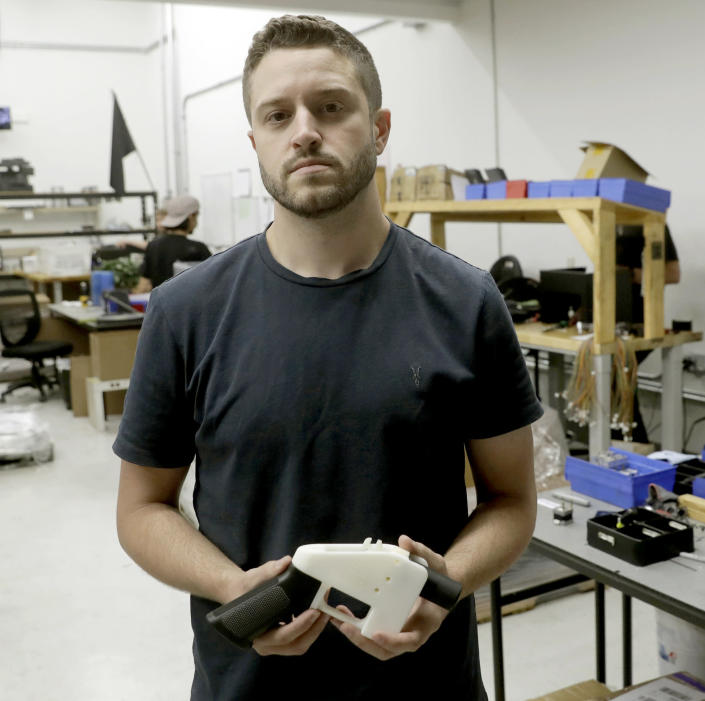 """FILE - In this Aug. 1, 2018, file photo, Cody Wilson, with Defense Distributed, holds a 3D-printed gun called the Liberator at his shop, in Austin, Texas. For a few hundred dollars, tools and some elbow grease, you can make your very own rifle or handgun. It's all perfectly legal _ and it can be done without leaving anything behind for the government to trace. These so-called """"ghost guns"""" have long been popular among hobbyists or gun enthusiasts. But gun-control advocates say they are increasingly popping up in crimes, used by people who are prohibited from buying a firearm and are trying to circumvent a background check. (AP Photo/Eric Gay, File)"""