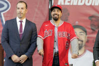 Los Angeles Angels' Anthony Rendon, right, reacts after putting on a jersey with general manager Billy Eppler during a baseball news conference in Anaheim, Calif., Saturday, Dec. 14, 2019. Rendon and the Angels agreed to a $245 million, seven-year contract earlier in the week. (AP Photo/Alex Gallardo)