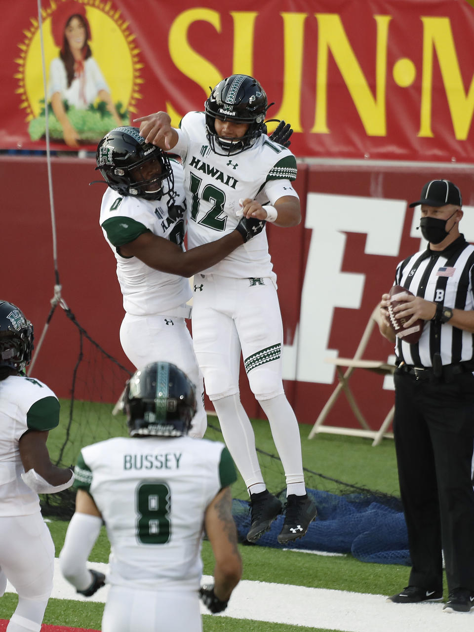 Hawaii quarterback Chevan Cordeiro, right, celebrates his touchdown with running back Dae Dae Hunter against Fresno State quarterback during the first half of an NCAA college football game in Fresno, Calif., Saturday, Oct. 24, 2020. (AP Photo/Gary Kazanjian)
