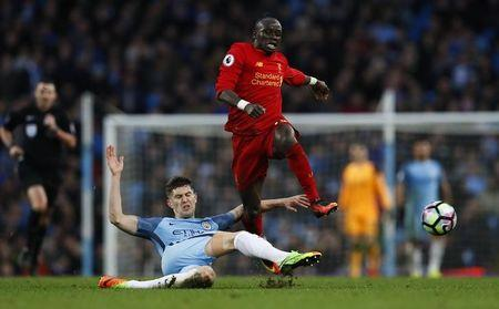 Manchester City's John Stones in action with Liverpool's Sadio Mane