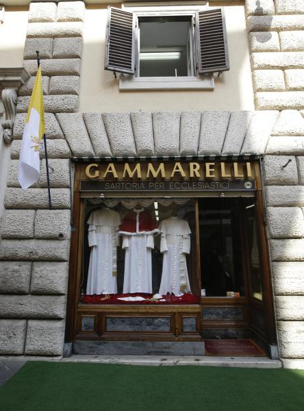 """In this photo taken on March 4, 2013, three sets of papal outfits - small, medium and large sizes - are displayed in the window of the tailoring shop Gammarelli, in Rome. The favorite guessing game in Rome these days is who will be the next pope. No one takes this more seriously than the Gammarelli family, ecclesiastical tailors by papal appointment for over 200 years. For the past seven conclaves Gammarelli has prepared three identical white outfits in small, medium and large for the new pope when he makes his first public appearance on the balcony of St.Peter's and gives his first blessing to the crowd below. The outfits have been on display in the window of the small wood paneled store nestled in the shadow of the Pantheon, where the family moved in 1850 from the original """"bottega'' (artisan shop) just around the corner founded in 1798. Before the start of the conclave, the outfits will be delivered to the Vatican, and left in a room adjacent to the Sistine Chapel, where the just elected pope will change into his new clothes. (AP Photo/Andrew Medichini)"""