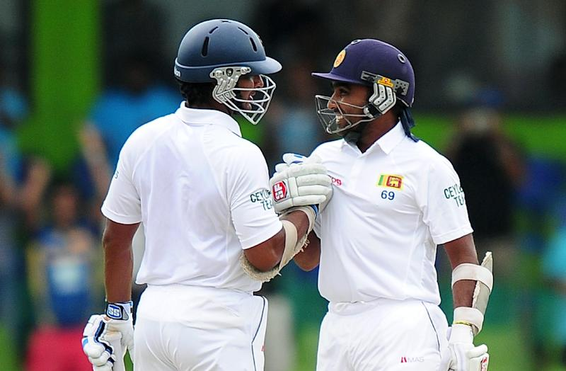 Sri Lankan cricketer Mahela Jayawardene (R) is congratulated by his teammate Kumar Sangakkara after scoring a half-century (50 runs) during the fourth day of the second Test match in Colombo on August 17, 2014 (AFP Photo/Lakruwan Wanniarachchi)