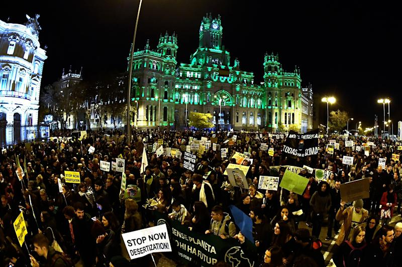 Demonstrators walk past the city hall on Cibeles Square during a mass climate march to demand urgent action on the climate crisis from world leaders attending the COP25 summit in Madrid on Friday. (Photo: OSCAR DEL POZO via Getty Images)
