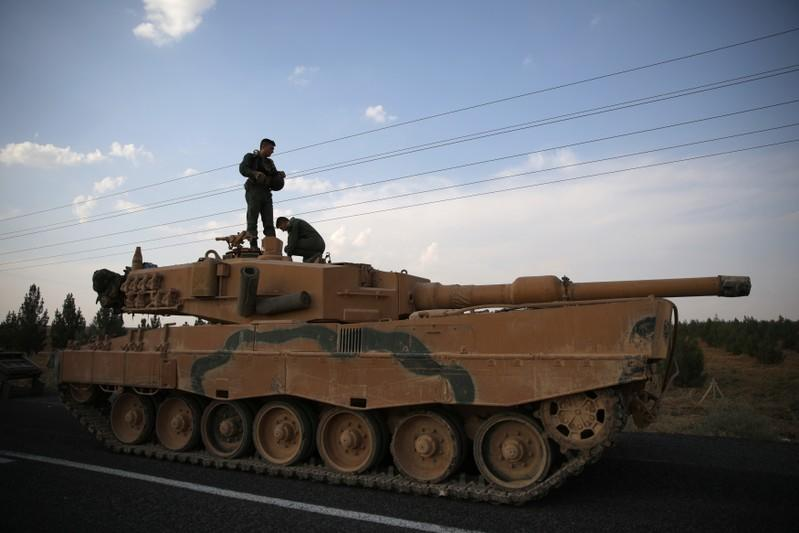 Turkish soldiers stand atop of a tank as army vehicles are moving on a road near the Turkish border town of Ceylanpinar
