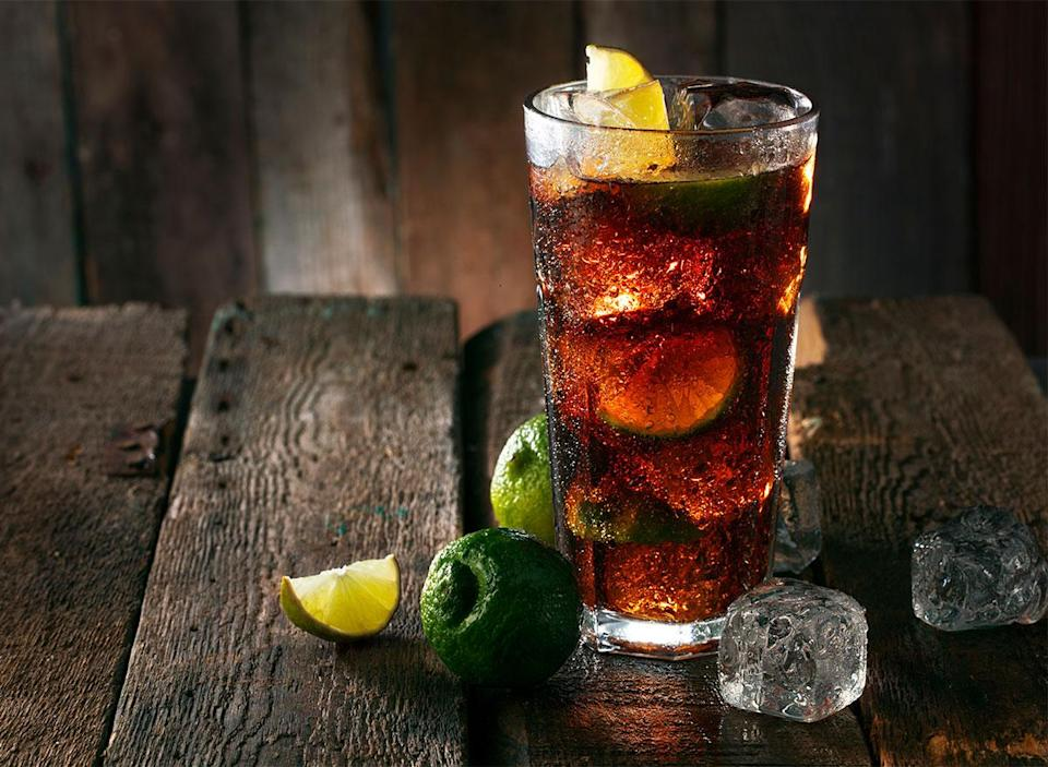 glass of coke with ice and lemon and lime wedges