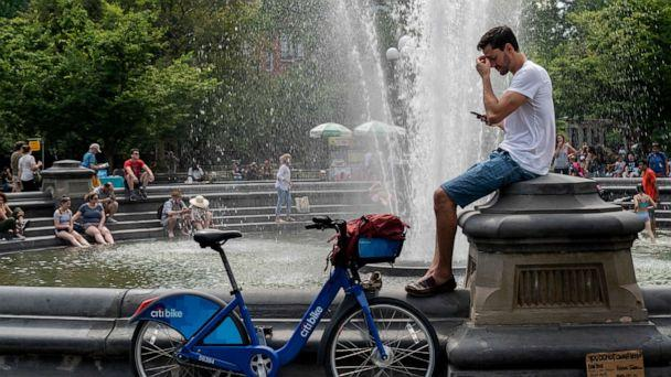 PHOTO: People cool off near the fountain at Washington Square Park during a hot afternoon day on July 17, 2019, in New York. (Drew Angerer/Getty Images)