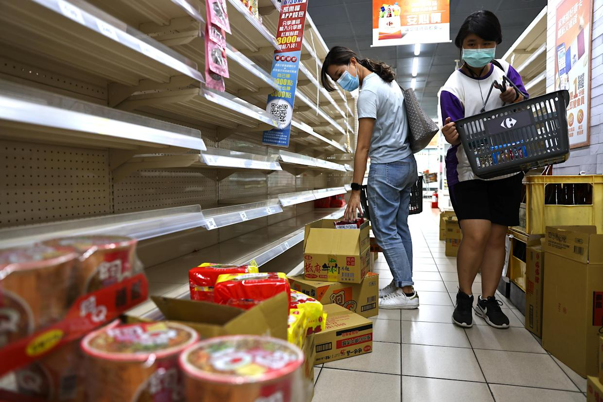 Two women wear protective face masks while shopping for instant noodles following a surge of coronavirus disease (COVID-19) infections in Taipei, Taiwan May 17, 2021. REUTERS/Ann Wang