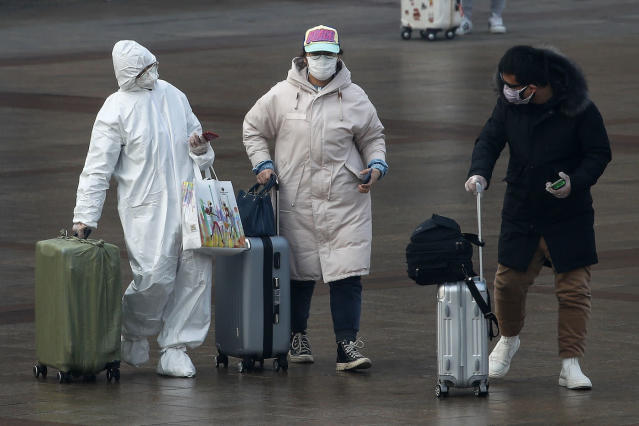 A passenger wearing a full-body protective suit walks out of Beijing railway station (AP)