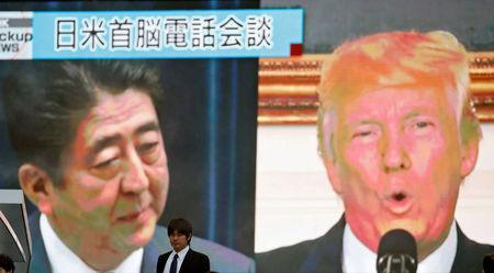 A man walks past a street monitor showing Japan's Prime Minister Shinzo Abe (L) and U.S. President Donald Trump in a news report about their telephone conference on North Korea's threat, in Tokyo, Japan, September 3, 2017. REUTERS/Toru Hanai/Files