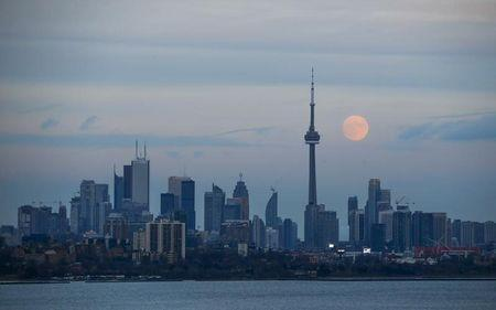 The moon rises behind the CN Tower, a Canadian landmark, and the skyline in Toronto, Canada November 24, 2015. REUTERS/Mark Blinch