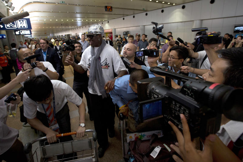 Retired NBA star Dennis Rodman, center, walks past journalists upon arriving at the Beijing capital airport in Beijing, China, Saturday, Sept. 7, 2013. Rodman left North Korea Saturday, professing his affection for autocratic leader Kim Jong Un and angrily rejecting calls for him to lobby for the release of imprisoned American citizen Kenneth Bae. (AP Photo/Ng Han Guan)