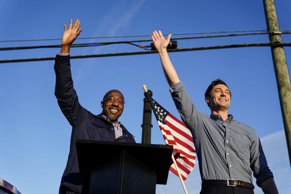FILE - In this Nov. 15, 2020, file photo Georgia Democratic candidates for U.S. Senate Raphael Warnock, left, and Jon Ossoff, right, gesture toward a crowd during a campaign rally in Marietta, Ga. (AP Photo/Brynn Anderson, File)