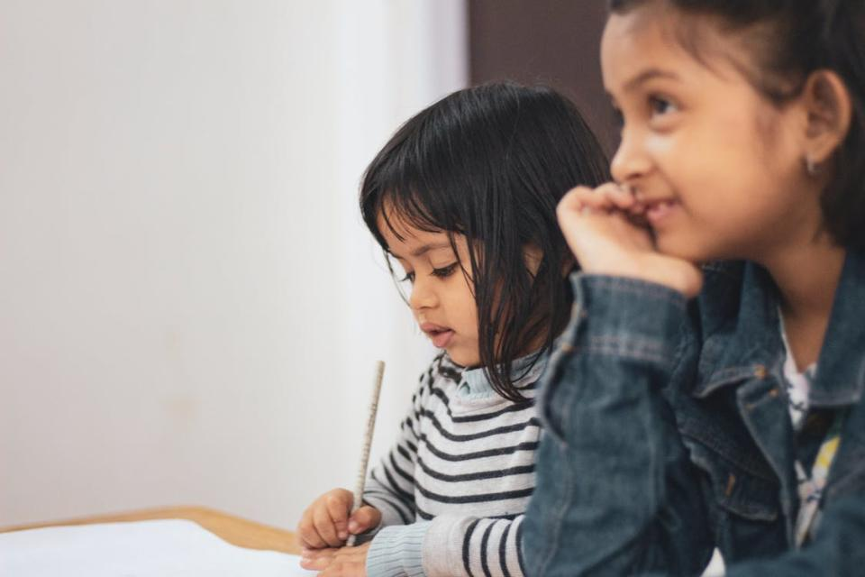 Two Girls Writing on Paper