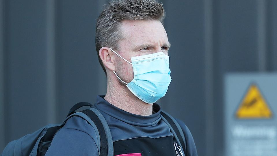 Collingwood coach Nathan Buckley is pictured wearing a face mask.