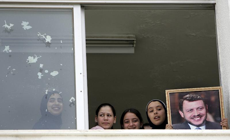 School children holding a picture of King Abdullah II watch out a window of the Swaifiyeh Secondary School for Girls in Amman on May 22, 2005