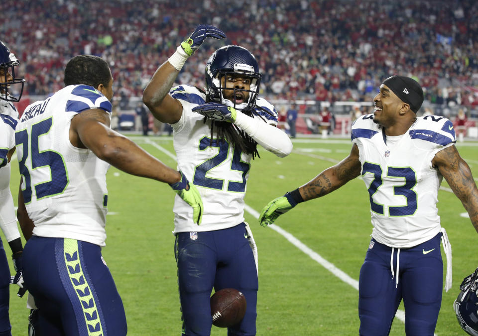 Seattle Seahawks cornerback Richard Sherman (25) celebrates his interception against the Arizona Cardinals with teammates Jeron Johnson (23) and DeShawn Shead (35) during the second half of an NFL football game, Sunday, Dec. 21, 2014, in Glendale, Ariz. (AP Photo/Ross D. Franklin)