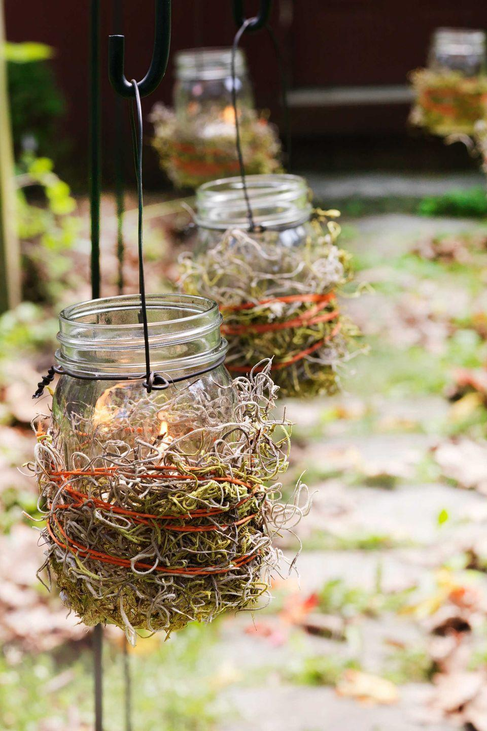 """<p>A flicker of battery-operated candlelight is just enough for trick-or-treaters to see their way to your front door. Wrap a 2"""" to 3"""" strip of <span class=""""redactor-unlink"""">adhesive-backed moss</span> around the jar; trim any extra. Loop some orange twine around the moss 3 to 4 times and knot to secure; tuck reindeer moss into the twine. Wrap the lip of the jar with baling wire (from a hardware stores) to make a handle. Pop in battery-operated tea lights; hang the lanterns from <span class=""""redactor-unlink"""">shepherd's hooks</span>.</p><p><strong>What You'll Need</strong>: <a href=""""https://www.amazon.com/Flameless-Candles-Battery-Holidays-Decoration/dp/B0799G5W6Y/ref=sr_1_3_sspa?dchild=1&keywords=tea+lights&qid=1594999561&sr=8-3-spons&psc=1&spLa=ZW5jcnlwdGVkUXVhbGlmaWVyPUEzVjZGOVZJSEZWMVFFJmVuY3J5cHRlZElkPUEwMTUzMTk0TEs3ODlJVkRFODYwJmVuY3J5cHRlZEFkSWQ9QTAyMjk0NTYzMUZQQTdPNko5N0dZJndpZGdldE5hbWU9c3BfYXRmJmFjdGlvbj1jbGlja1JlZGlyZWN0JmRvTm90TG9nQ2xpY2s9dHJ1ZQ%3D%3D&tag=syn-yahoo-20&ascsubtag=%5Bartid%7C10070.g.1279%5Bsrc%7Cyahoo-us"""" rel=""""nofollow noopener"""" target=""""_blank"""" data-ylk=""""slk:Mini tea lights"""" class=""""link rapid-noclick-resp"""">Mini tea lights</a> ($8, Amazon); <a href=""""https://www.amazon.com/Aleenes-Purpose-Tacky-Adhesive-11-Ounce/dp/B001689P10/ref=sr_1_13?dchild=1&keywords=adhesive+moss&qid=1594999608&sr=8-13&tag=syn-yahoo-20&ascsubtag=%5Bartid%7C10070.g.1279%5Bsrc%7Cyahoo-us"""" rel=""""nofollow noopener"""" target=""""_blank"""" data-ylk=""""slk:adhesive spray"""" class=""""link rapid-noclick-resp"""">adhesive spray</a> ($10, Amazon); <a href=""""https://www.amazon.com/Super-Moss-59834-23310-B00I6AKFI8/dp/B00I6AKFI8/ref=sr_1_7?dchild=1&keywords=moss&qid=1594999647&sr=8-7&th=1&psc=1&tag=syn-yahoo-20&ascsubtag=%5Bartid%7C10070.g.1279%5Bsrc%7Cyahoo-us"""" rel=""""nofollow noopener"""" target=""""_blank"""" data-ylk=""""slk:moss"""" class=""""link rapid-noclick-resp"""">moss </a>($8, Amazon); </p>"""