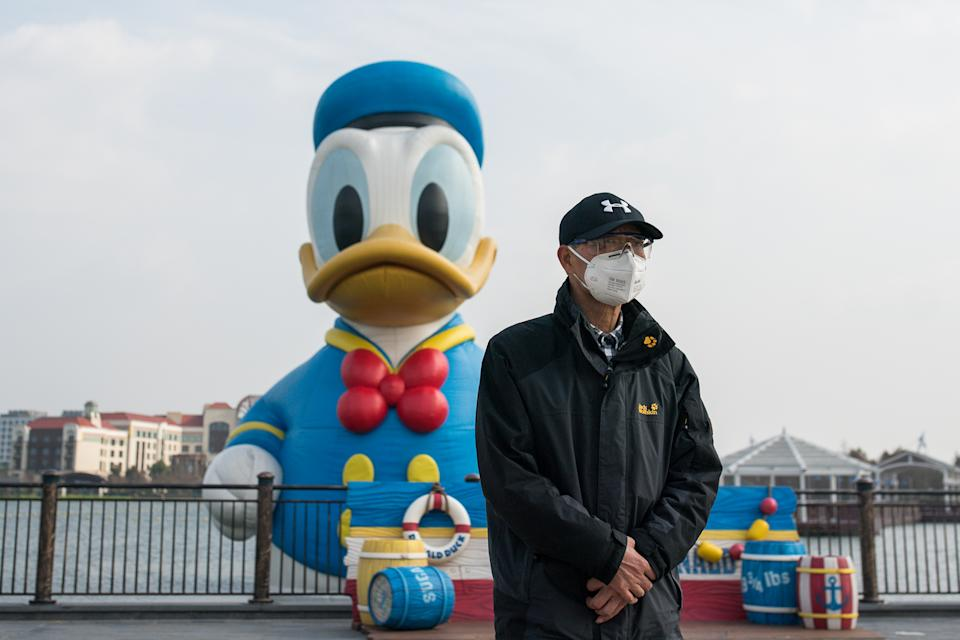 """SHANGHAI, CHINA - MARCH 10: A tourist wearing a protective mask and protective glasses walks by a floating sculptures of Donald Duck in Shanghai Disneyland Park on March 10, 2020 in Shanghai, China. The Shanghai Disney Resort has said it will reopen some of the shopping, dining and entertainment options on Monday, though the main theme park will remain closed to prevent further spread of the coronavirus. Twenty-one of mainland China's 31 regions have lowered emergency response levels on the flu-like epidemic by March 1, allowing greater movement of people and goods and a recovery in business activity. Since the outbreak began in December last year, more than 80,000 cases have been confirmed in China, with the death toll rising to more than 3,100. As of today, the number of cases of new coronavirus COVID-19 being treated in China dropped to approximately 17,800 in China. The World Health Organization (WHO) declared to raises coronavirus threat assessment to """"very high"""" globally by the end of February. (Photo by Yifan Ding/Getty Images)"""