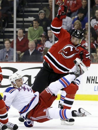 New York Rangers right wing Darroll Powe, bottom, is checked by New Jersey Devils right wing Dainius Zubrus, of Lithuania, during the second period of an NHL hockey game, Tuesday, Feb. 5, 2013, in Newark, N.J. (AP Photo/Julio Cortez)