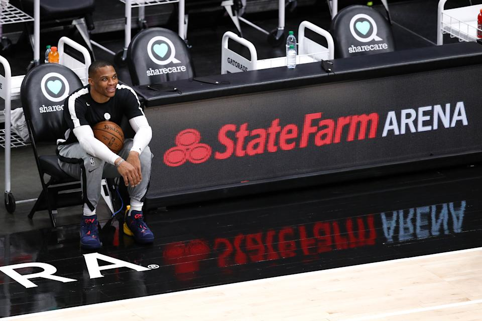 Russell Westbrook smiles while sitting on the bench holding a basketball during pregame warmups.